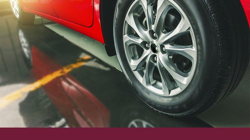 """Imagem de um pneu de um carro vermelho, ilustrando o artigo """"Quando trocar os pneus do carro?"""""""