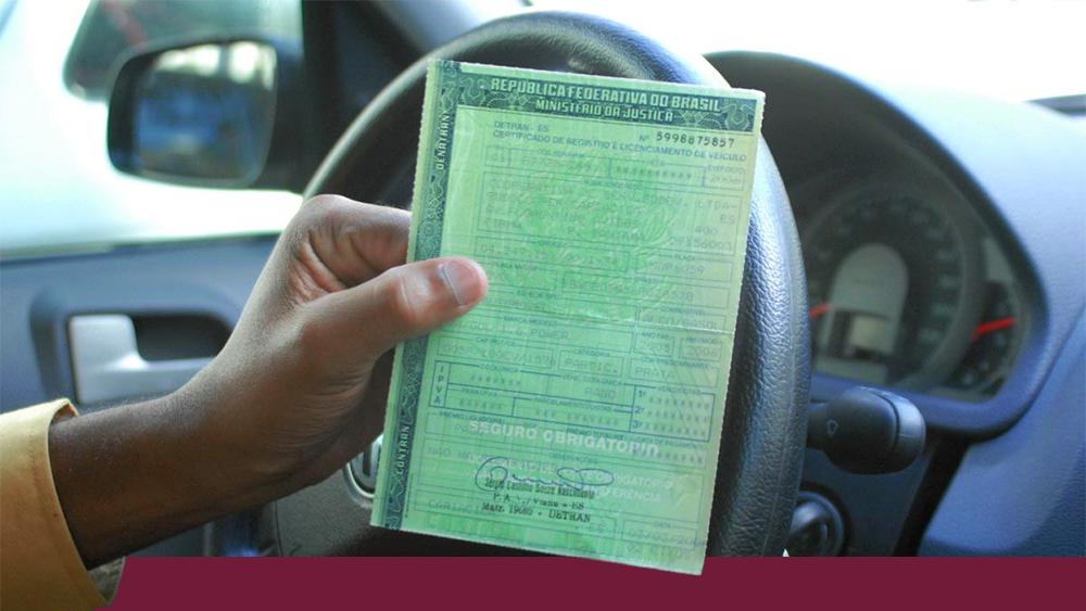 Motorista mostrando documento de IPVA atrasado